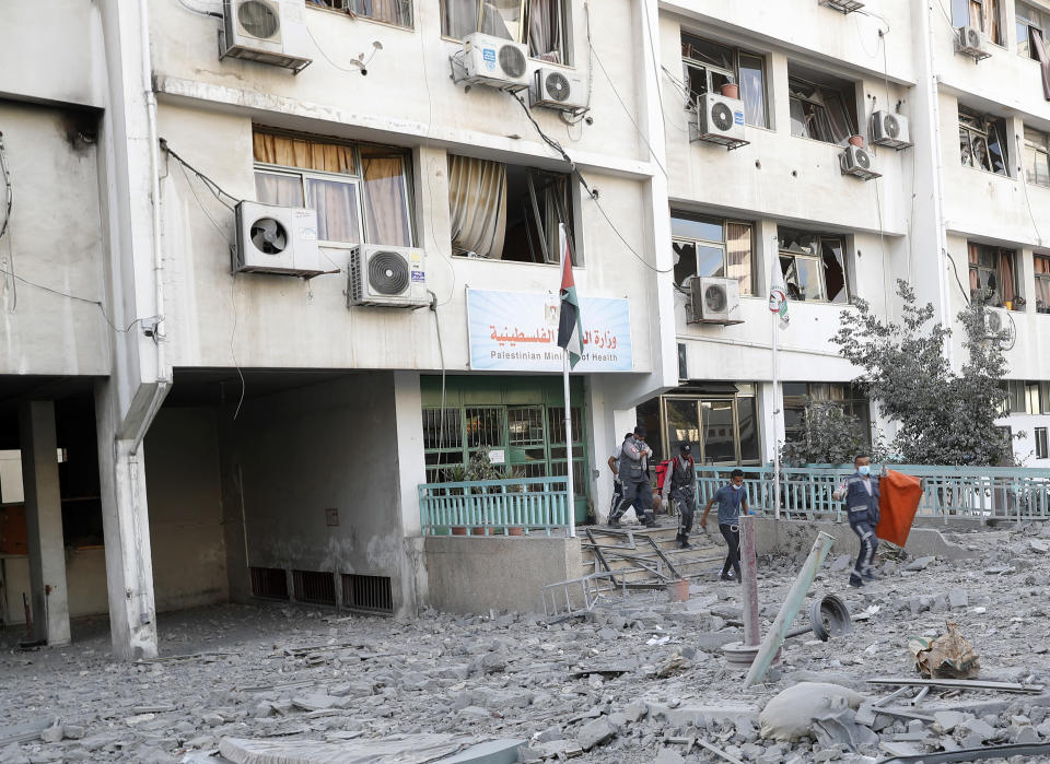FILE - In this May 17, 2021, file photo, medics inspect the rubble of Gaza health care clinic following an Israeli airstrike on the upper floors of a commercial building near the Health Ministry in Gaza City. The Gaza Strip's already feeble health system is being brought to its knees by the fourth war in just over a decade. (AP Photo/Adel Hana, File)