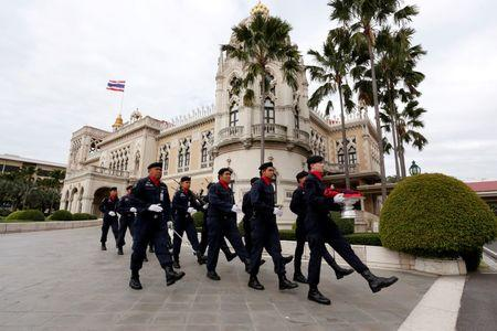 Soldiers carry Thailand's national flag before raising it at The Government House in Bangkok