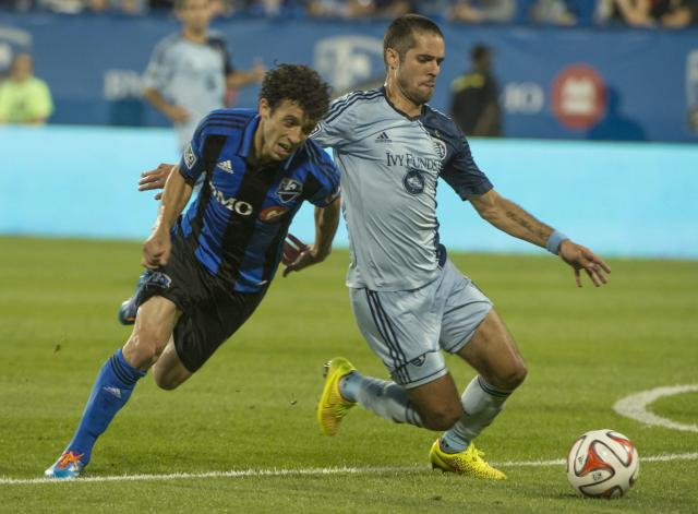 Montreal Impact's Felipe Martins and Sporting Kansas City's Benny Feilhaber battle for the ball during the second half of a soccer game, Saturday, July 12, 2014 in Montreal. (AP Photo/The Canadian Press, Peter McCabe)
