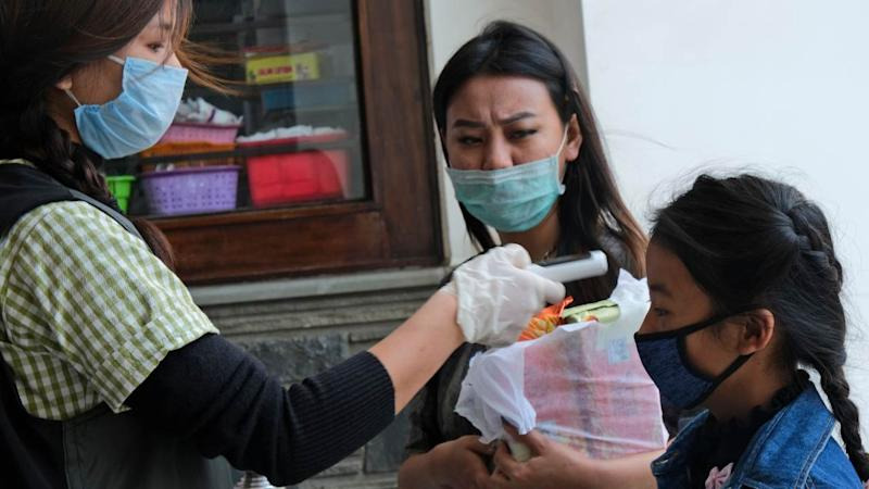 A medical staff checks the temperature of a girl at the entrance of Oking Hospital in Kohima, capital of the northeastern Indian state of Nagaland, Monday, April 13, 2020. A man from Nagaland state has tested positive for COVID- 19, becoming the first case from the state. The new coronavirus causes mild or moderate symptoms for most people, but for some, especially older adults and people with existing health problems, it can cause more severe illness or death. (AP Photo/Yirmiyan Arthur)