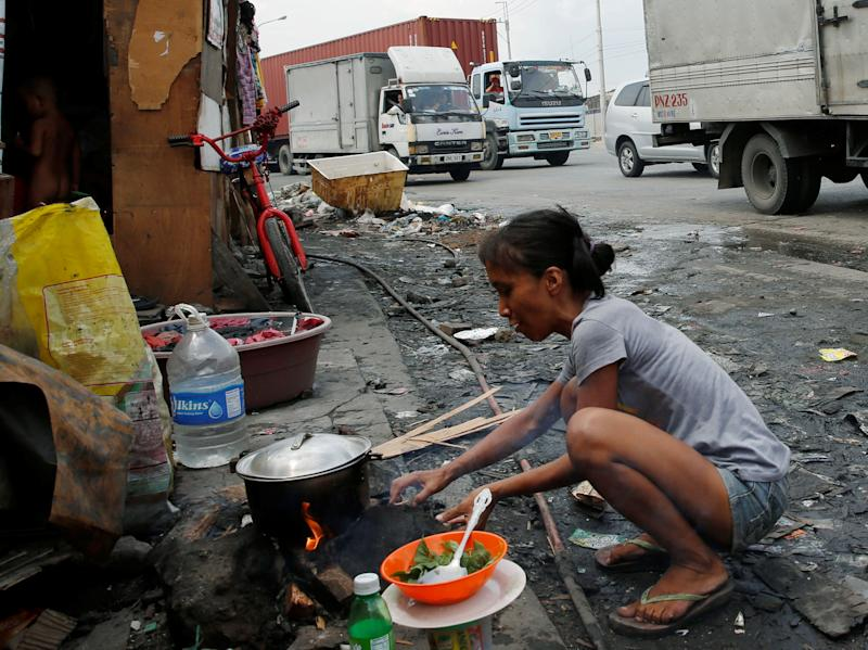 A housewife whose family lives in a shanty cooks beside a road in Manila, Philippines May 25, 2016. REUTERS/Erik De Castro