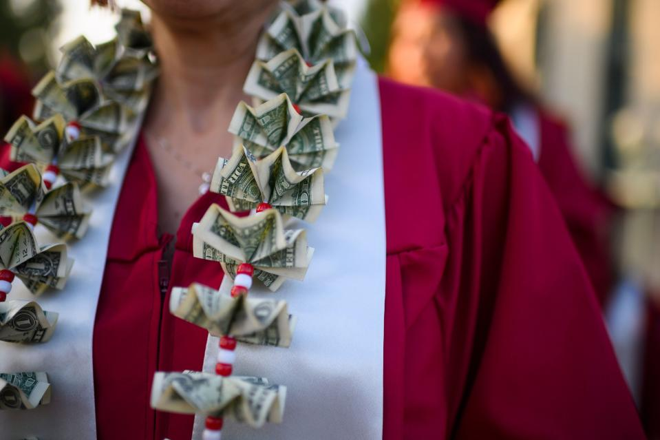 """A graduating student wears a money lei, a necklace made of US dollar bills, at the Pasadena City College graduation ceremony, June 14, 2019, in Pasadena, California. - With 45 million borrowers owing $1.5 trillion, the student debt crisis in the United States has exploded in recent years and has become a key electoral issue in the run-up to the 2020 presidential elections. """"Somebody who graduates from a public university this year is expected to have over $35,000 in student loan debt on average,"""" said Cody Hounanian, program director of Student Debt Crisis, a California NGO that assists students and is fighting for reforms. (Photo by Robyn Beck / AFP)        (Photo credit should read ROBYN BECK/AFP/Getty Images)"""