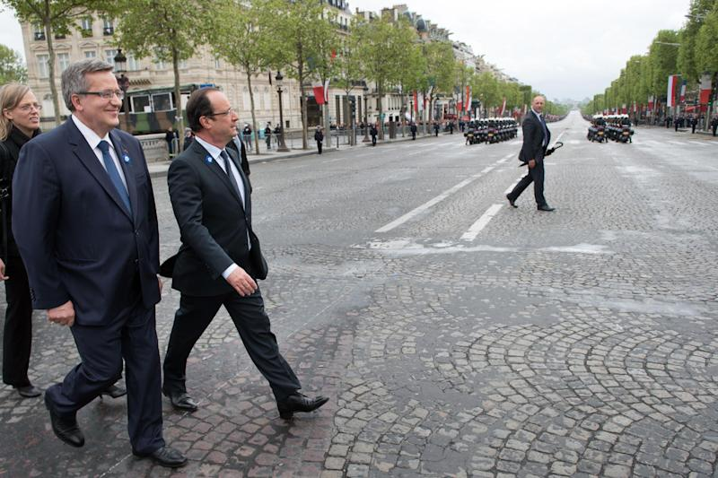 Polish President Bronislaw Komorowski, left, and French President Francois Hollande, right, walks across the Champs Elysee avenue during a ceremony marking the 68th anniversary of the end of World War II in Europe, in Paris, Wednesday, May 8, 2013. (AP Photo/Bertrand Langlois, Pool)