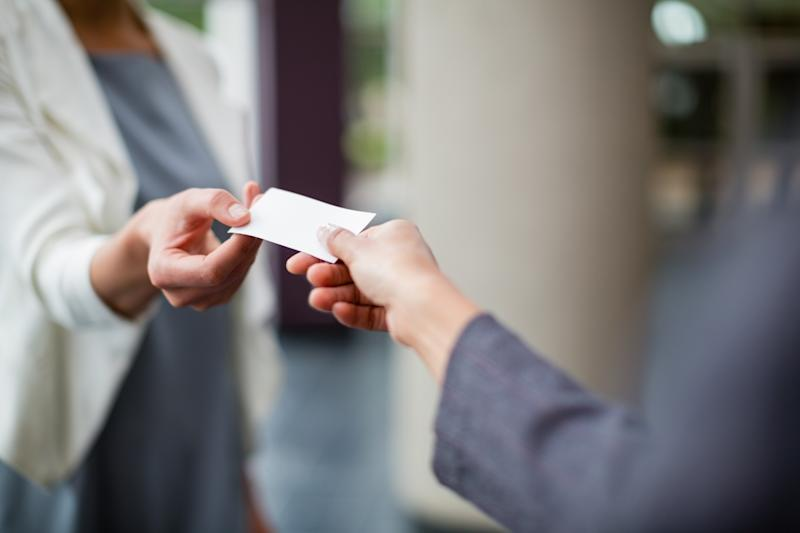 Woman handing another woman her business card.