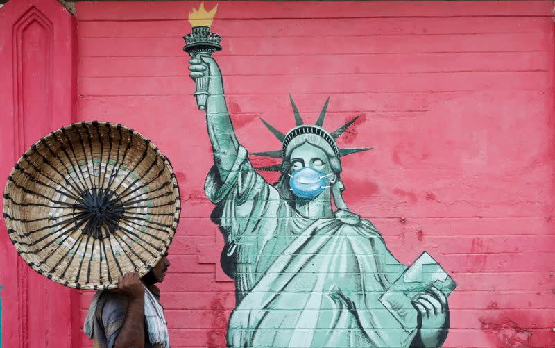 Man carrying a basket walks past a graffiti depicting the Statue of Liberty wearing a mask amidst the spread of the coronavirus disease, in Mumbai