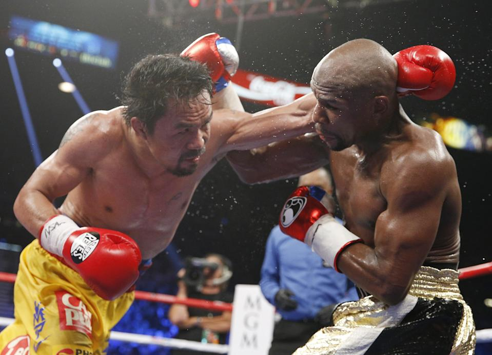 Manny Pacquiao trades blows with Floyd Mayweather Jr. during their welterweight title fight on Saturday, May 2, 2015 in Las Vegas. (AP)