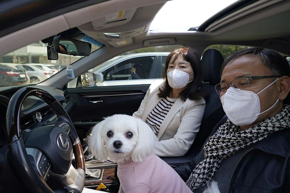 South Korean Christians wearing protective face masks sit with a dog during a drive-in worship service following the outbreak of the coronavirus disease (COVID-19) in Seoul, South Korea, April 5, 2020. REUTERS/Kim Hong-Ji