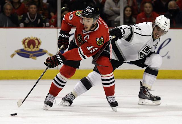 Chicago Blackhawks' Jonathan Toews (19) controls the puck against Los Angeles Kings' Anze Kopitar (11) during the second period in Game 1 of the Western Conference finals in the NHL hockey Stanley Cup playoffs in Chicago on Sunday, May 18, 2014. (AP Photo/Nam Y. Huh)