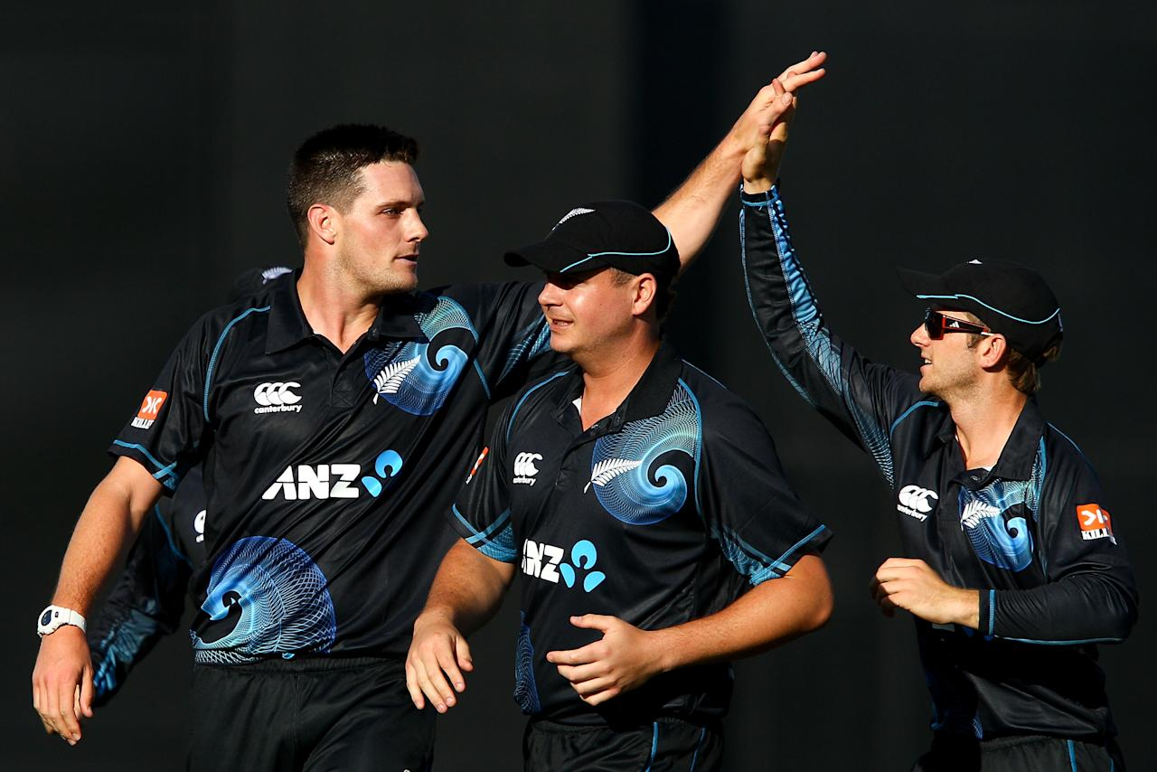 NAPIER, NEW ZEALAND - JANUARY 19:  L to R, Mitchell McClenaghan of New Zealand celebrates with Jesse Ryder and Kane Williamson after taking the wicket of Rohit Sharma of India during the first One Day International match between New Zealand and India at McLean Park on January 19, 2014 in Napier, New Zealand.  (Photo by Hagen Hopkins/Getty Images)