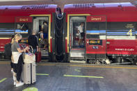 Passengers, including American tourist Riley Smith, left, board a high-speed train to to Rome, Naples and Reggio Calabria in southern Italy from Florence's Santa Maria Novella train station, Italy, Wednesday, Sept. 1, 2021. The Italian government vowed to crack down on demonstrators threatening to block train tracks throughout the country on Wednesday as a rule requiring COVID-19 tests or vaccines takes effect for long-distance domestic public transport. (AP Photo/Karl Ritter)