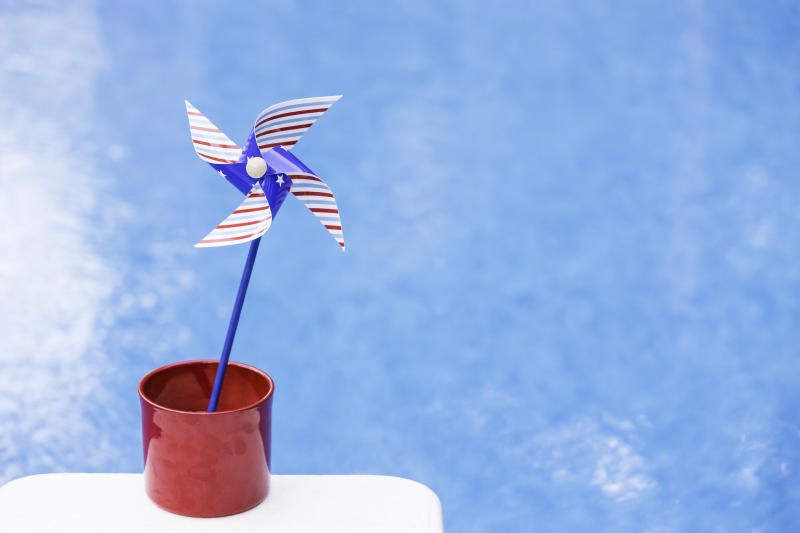 Red, white & blue pinwheel or whirligig in red pot with shimmering pool backdrop.