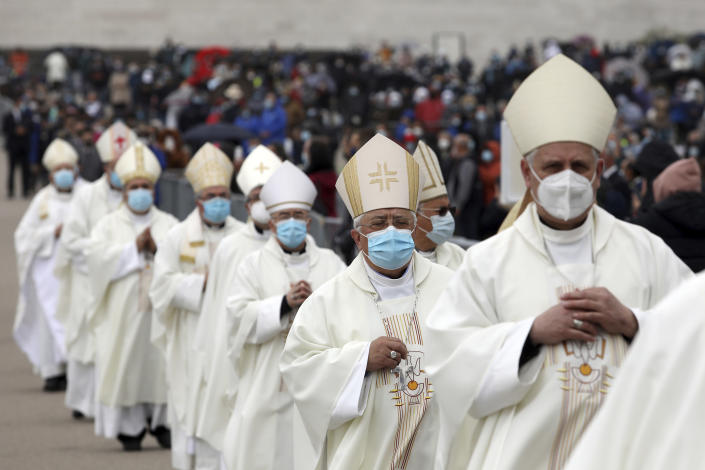 Clerics wear face masks while taking part in a procession in a procession before a mass during ceremonies at the Catholic shrine in Fatima, Portugal, Thursday, May 13, 2021. In view of the coronavirus pandemic, the shrine has limited to 7,500 the number of pilgrims that can be present during this year's May 12 and 13 celebrations usually attended by hundreds of thousands. (AP Photo/Ana Brigida)