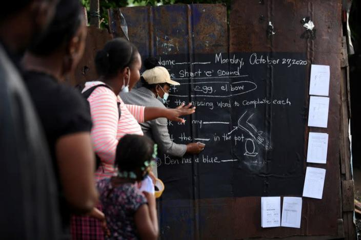 Educator Mckoy Phipps writes a lesson on a blackboard painted on a zinc fence during the coronavirus disease (COVID-19) outbreak in Kingston