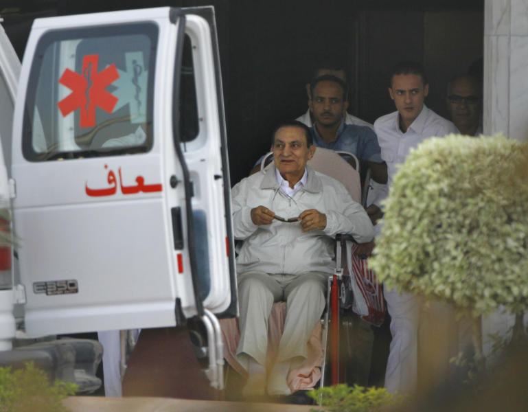 FILE - In this file photo taken Sunday, Aug. 25, 2013, former Egyptian President Hosni Mubarak, 85, is escorted by medical and security personnel into an ambulance to be taken by helicopter ambulance from Maadi Military Hospital to the Cairo Police Academy-turned-court in Cairo, Egypt. Egypt's ousted long-time autocrat went back in court Saturday, Sept. 14, 2013, as his trial resumed on charges related to the killings of some 900 protesters during the 2011 uprising that led to his ouster. (AP Photo/Amr Nabil, File)