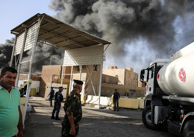 Iraqi federal policemen stand outside the country's biggest ballot warehouse hit by a fire and where votes for the eastern Baghdad district were stored on June 10, 2018 (AFP Photo/SABAH ARAR)