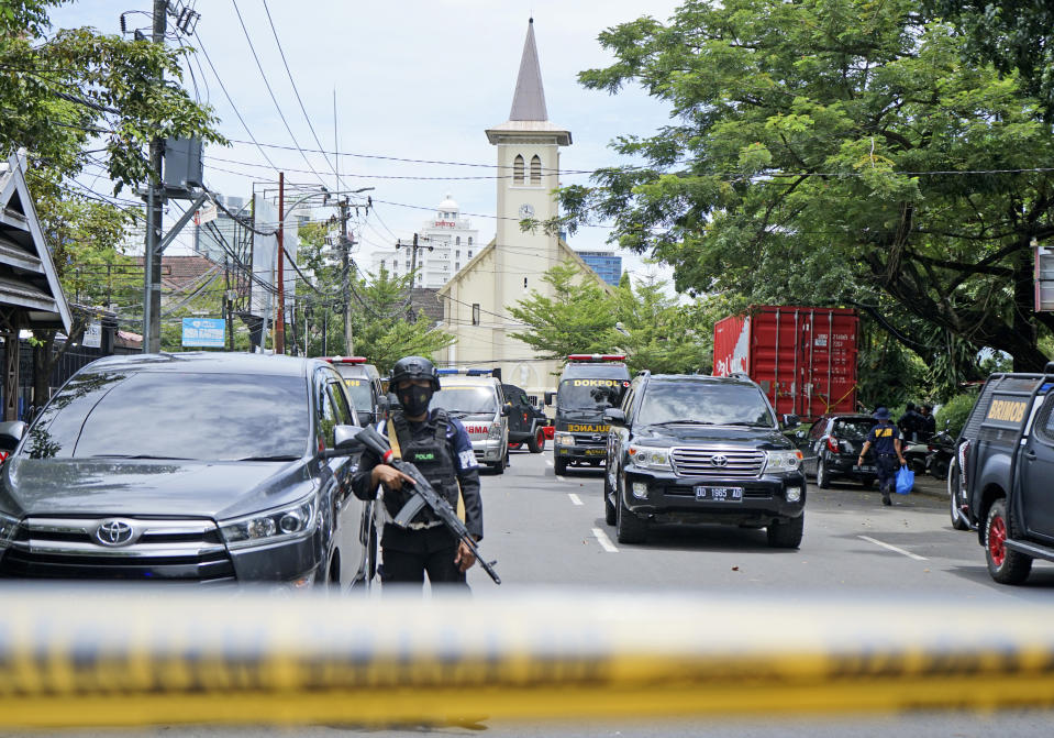 A police officer stands guard near a church where an explosion went off in Makassar, South Sulawesi, Indonesia, Sunday, March 28, 2021. Police in Indonesia say at least one suicide bomber has detonated outside a packed Roman Catholic cathedral during Sunday Mass, wounding several people. (AP Photo/Daeng Mansur)