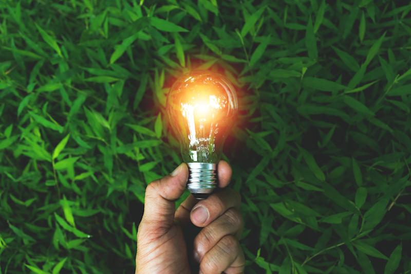 A man's hand holds a lit Edison bulb in front of a background of grass