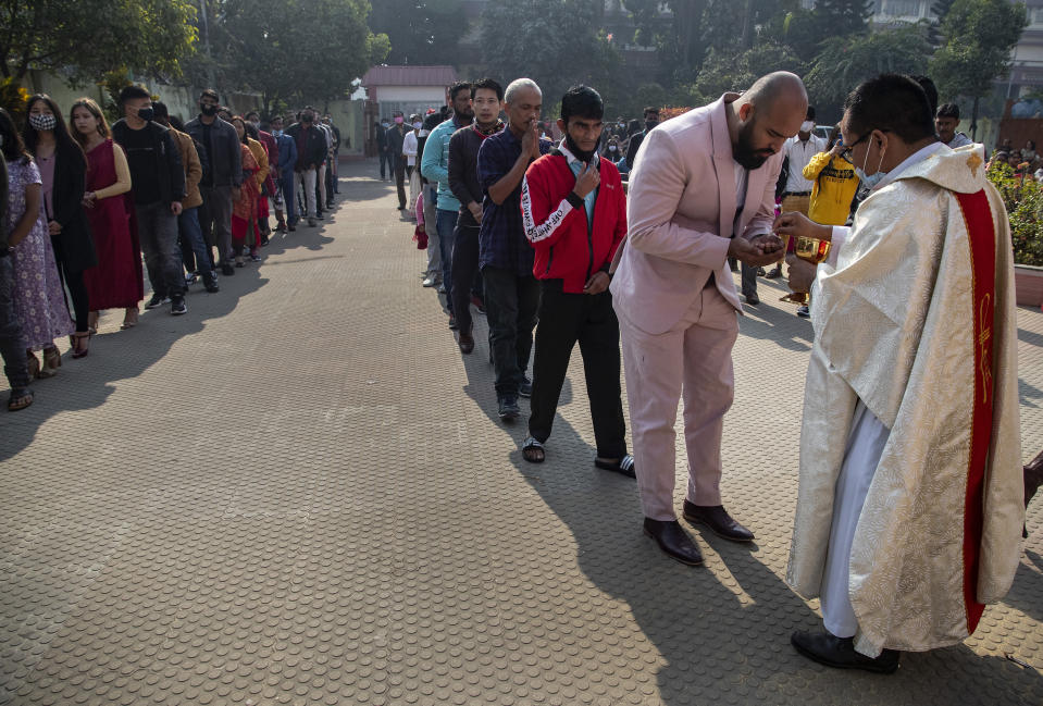 Indian Christians, many wearing face masks as a precaution against the coronavirus, line up to receive holy communion from the priest outside a church on Christmas in Gauhati, India, Friday, Dec. 25, 2020. (AP Photo/Anupam Nath)