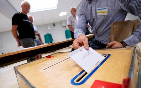 A ballot envelope is put in ballot box at a polling station in Tomelilla Sweden