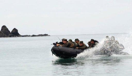 Philippine and US marines aboard a rubber boat speed towards the beach of Tagcauayan during a military exercise