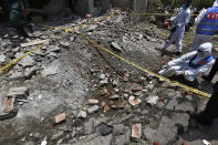 Investigators collect evidence at the site of explosion, in Lahore, Pakistan, Wednesday, June 23, 2021. A powerful explosion ripped through a residential area in the eastern city of Lahore on Wednesday, killing some people and injuring some others, police and rescue officials said. (AP Photo/K.M. Chaudary)
