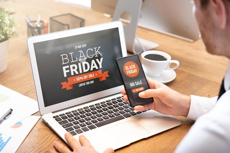Black Friday promotion sale on laptop and phone screen. Young man doing shopping online