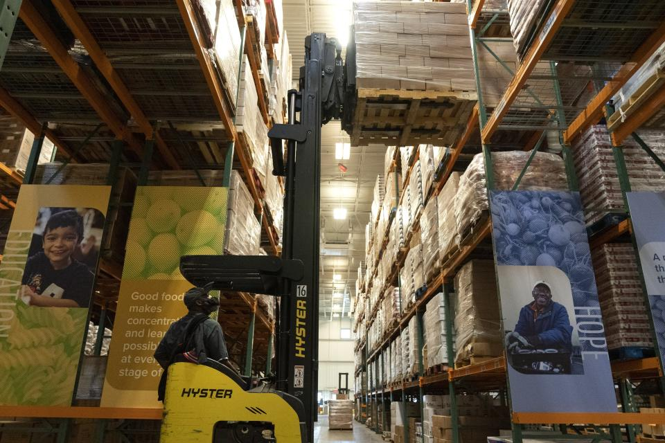 A worker loads the warehouse with food items at The Capital Area Food Bank, Tuesday, Oct. 5, 2021, in Washington. (AP Photo/Jacquelyn Martin)