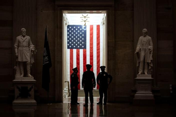 U.S. Capitol Police officers stand in front of an American flag in the Rotunda of the U.S. Capitol