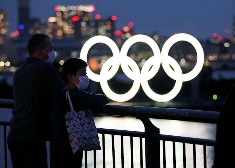 The giant Olympic rings are seen in front of the visitors wearing protective face masks, only a quarter of the Japanese public are excited about next year's reorganised Games according to one survey