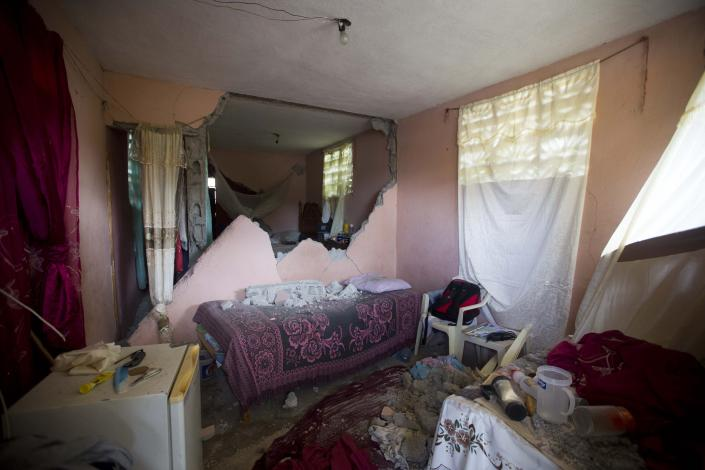 A bed is covered by rubble from a wall that collapsed during a magnitude 5.9 earthquake the night before, in Gros Morne, Haiti, Sunday, Oct. 7, 2018. Emergency teams worked to provide relief in Haiti on Sunday after the quake killed at least 11 people and left dozens injured. ( AP Photo/Dieu Nalio Chery)