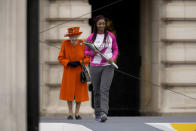 Baton bearer Britain's Kadeena Cox, who won two gold medals at the Rio 2016 Paralympic Games, receives the baton from Britain's Queen Elizabeth II at the Birmingham 2022 Commonwealth Games Queen's Baton Relay event outside Buckingham Palace in London, Thursday, Oct. 7, 2021. The city of Birmingham in England will host the 2022 Commonwealth Games. (AP Photo/Matt Dunham)