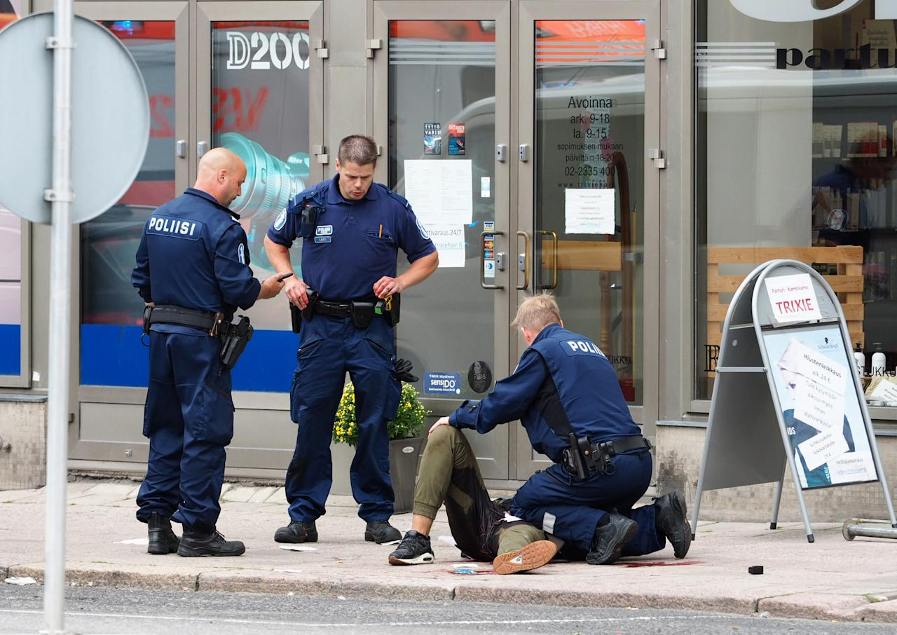 <p>Police officers stand next to a person lying on the pavement in the Finnish city of Turku where several people were stabbed on Aug. 18, 2017. (Kirsi Kanerva/AFP/Getty Images) </p>