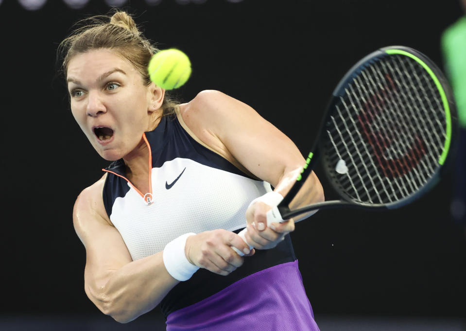 Romania's Simona Halep hits a backhand return to United States' Serena Williams during their quarterfinal match at the Australian Open tennis championship in Melbourne, Australia, Tuesday, Feb. 16, 2021.(AP Photo/Hamish Blair)
