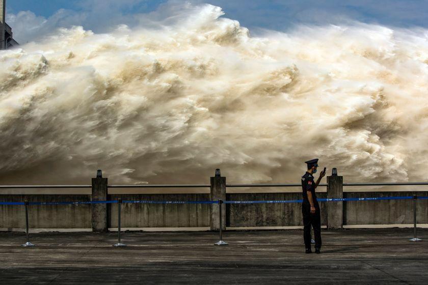 "A security guard looks at his smartphone as water is released from China's Three Gorges Dam on July 19 to relieve pressure from flooding. <span class=""copyright"">(Getty Images)</span>"