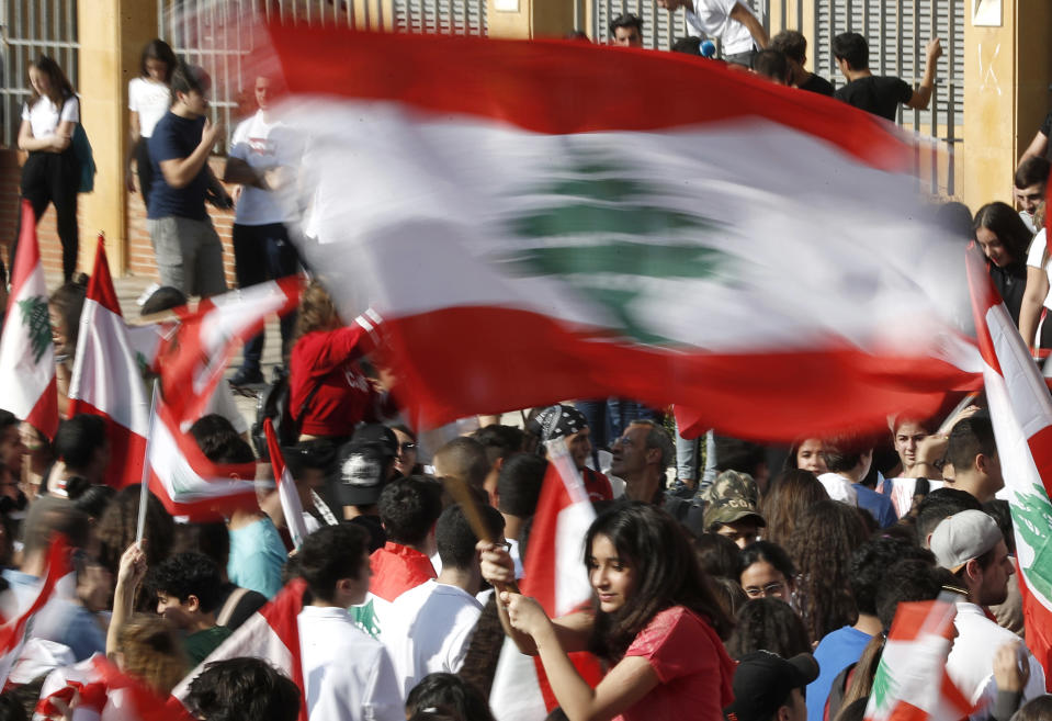 A student protester waves her national flag during protest against the government in front of the education ministry in Beirut, Lebanon, Friday, Nov. 8, 2019. Lebanese protesters are rallying outside state institutions and ministries to keep up the pressure on officials to form a new government to deal with the country's economic crisis. (AP Photo/Hussein Malla)