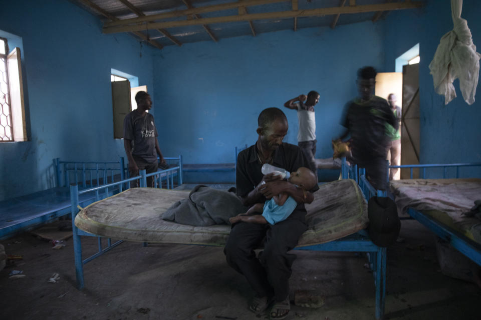 Tigrayan refugee Abraha Kinfe Gebremariam, 40, feeds his 4-month old daughter, Aden, inside their shelter in Hamdayet, eastern Sudan, near the border with Ethiopia, on March 21, 2021. Their village of Mai Kadra was the first known massacre of a conflict in which thousands of ethnic Tigrayans like his family have been killed. (AP Photo/Nariman El-Mofty)