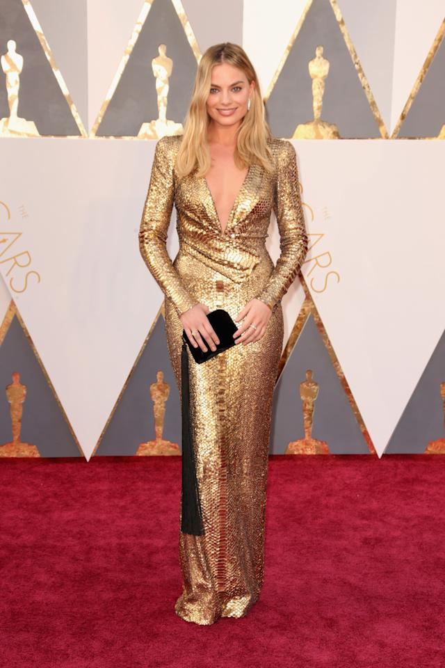 <p>Robbie gives new meaning to golden goddess with her gold DVF gown. She accessorized with a cute clutch with a long tassel. <i>(Photo: Getty Images)</i></p>