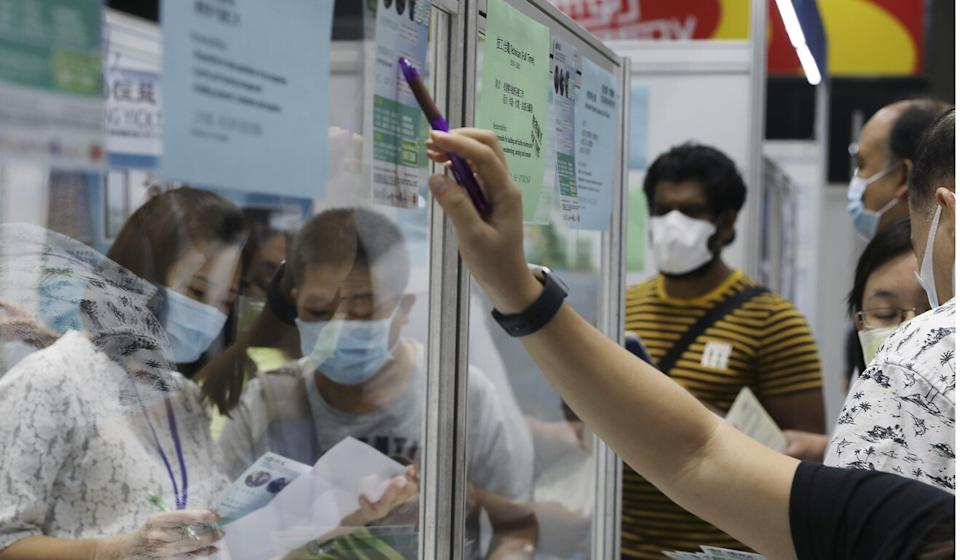 Jobseekers fill out application forms at an employment fair organised by the Labour Department at Southorn Stadium in Wan Chai on October 28, 2020. Photo: Nora Tam