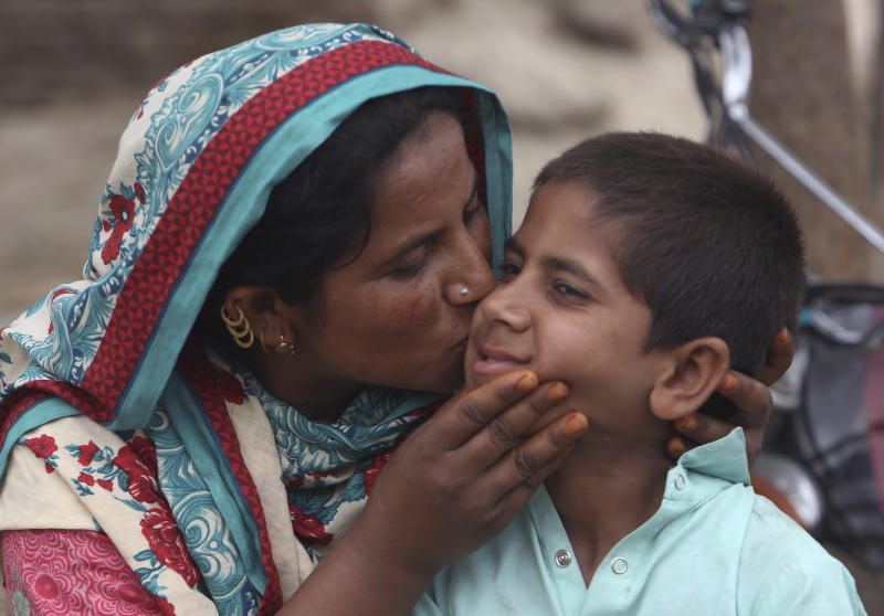 A Pakistani mother kisses her son Ali Raza, 10, infected with HIV in a village near Ratodero, a small town in southern province of Sindh in Pakistan, Thursday, May 16, 2019. Officials say about 500 people, mostly children, have tested positive for HIV, the virus that causes AIDS, in a southern Pakistani provincial district. A local doctor who has AIDS has since been arrested and is being investigated for possibly intentionally infecting patients. (AP Photo/Fareed Khan)
