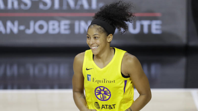 Candace Parker in a yellow Sparks jersey smiles.