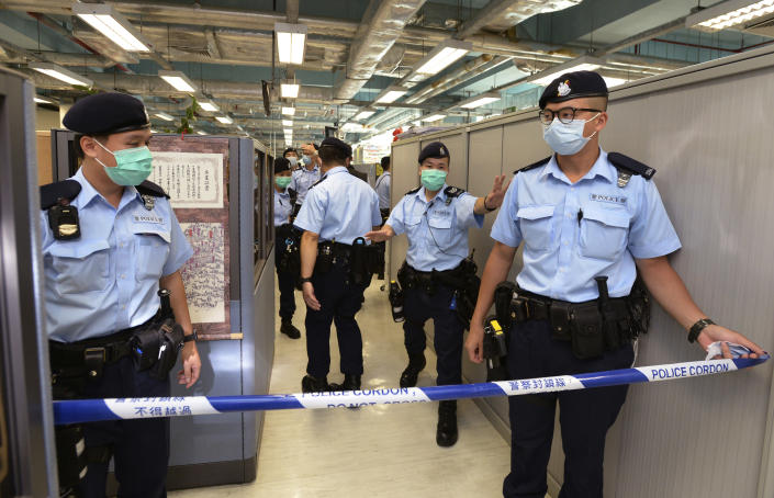 Police officers set up cordon line inside the Apple Daily newspaper headquarters after Hong Kong media tycoon and newspaper founder Jimmy Lai was arrested at his home in Hong Kong, Monday, Aug. 10, 2020. Hong Kong police arrested Lai and raided the publisher's headquarters Monday in the highest-profile use yet of the new national security law Beijing imposed on the city after protests last year. (Apple Daily via AP)