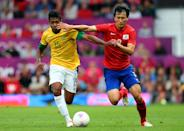 MANCHESTER, ENGLAND - AUGUST 07: Alex Sandro of Brazil holds off Ji Dongwon of Korea during the Men's Football Semi Final match between Korea and Brazil, on Day 11 of the London 2012 Olympic Games at Old Trafford on August 7, 2012 in Manchester, England. (Photo by Stanley Chou/Getty Images)