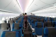 FILE PHOTO: A stewardess with Singapore Airlines walks through the economy seating of the airline's Boeing 787-10 Dreamliner after a delivery ceremony at the Boeing South Carolina plant in North Charleston