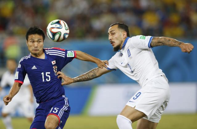 Japan's Yasuyuki Konno (L) and Greece's Konstantinos Mitroglou fight for the ball during their 2014 World Cup Group C soccer match at the Dunas arena in Natal June 19, 2014. REUTERS/Toru Hanai (BRAZIL - Tags: SOCCER SPORT WORLD CUP)