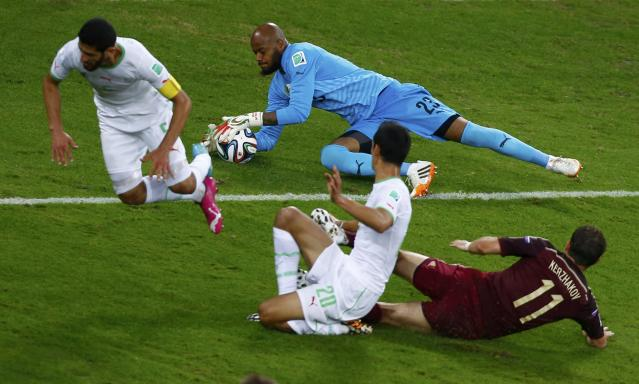 Algeria's goalkeeper Rais Mbolhi (23) makes a save near his teammate Rafik Halliche (L) as Russia's Alexander Kerzhakov watches during their 2014 World Cup Group H soccer match at the Baixada arena in Curitiba June 26, 2014. REUTERS/Amr Abdallah Dalsh (BRAZIL - Tags: SOCCER SPORT WORLD CUP)