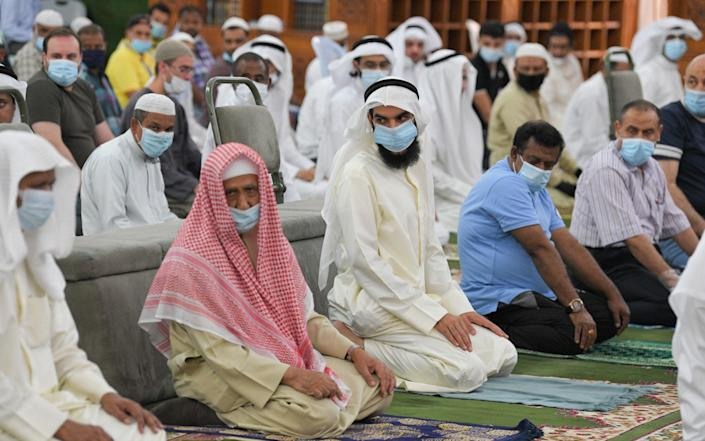People perform their first Friday prayer at a mosque in Kuwait after it reopened for the first time since March