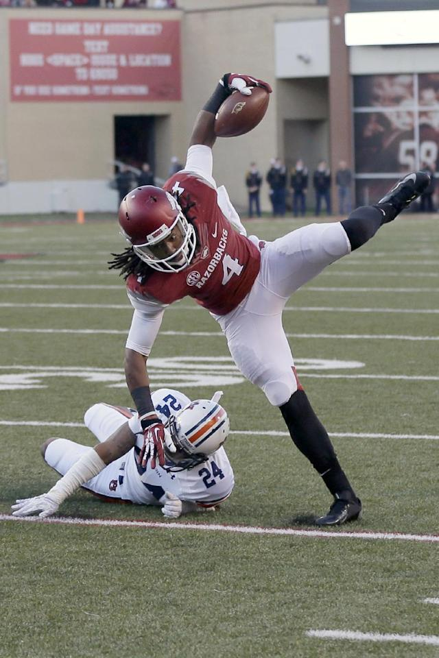 Arkansas wide receiver Keon Hatcher (4) trips over Auburn defensive back Ryan Smith during the second quarter of an NCAA college football game in Fayetteville, Ark., Saturday, Nov. 2, 2013. (AP Photo/Danny Johnston)