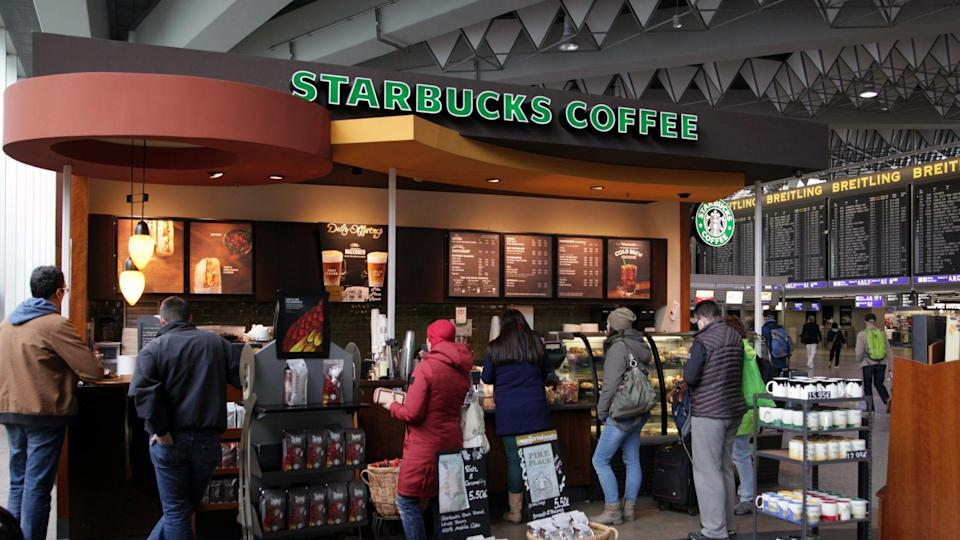 Frankfurt, Germany - April 27, 2016: Passengers waiting for their flight queuing at a Starbucks cafe and snack bar for a small drink or piece of cake at Frankfurt Airport.