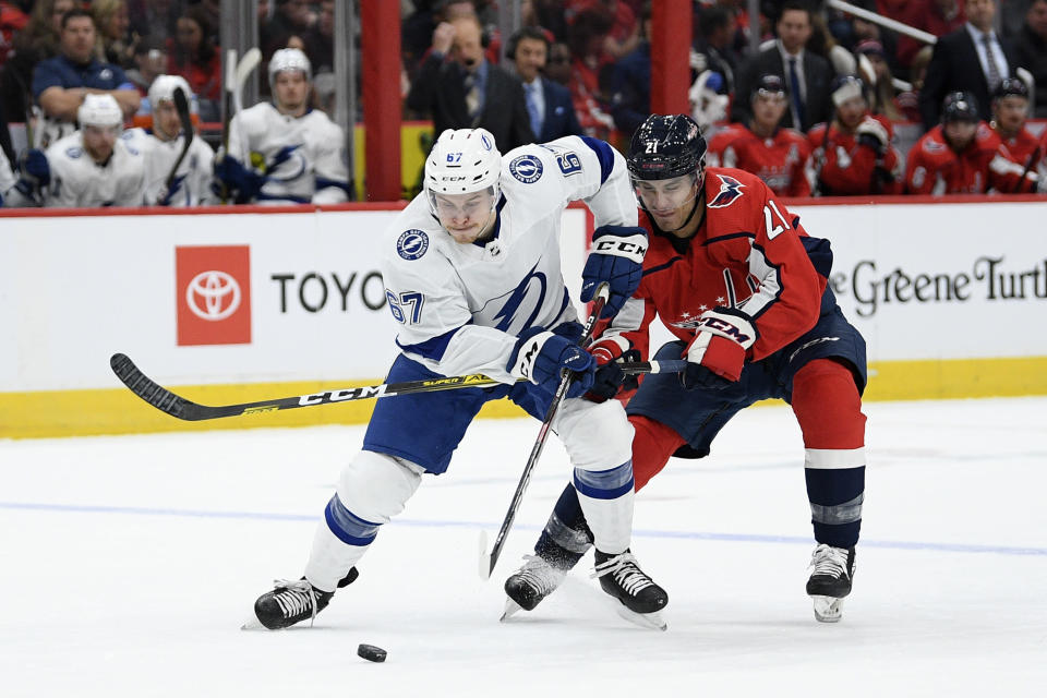Tampa Bay Lightning center Mitchell Stephens (67) and Washington Capitals right wing Garnet Hathaway (21) battle for the puck during the second period of an NHL hockey game, Saturday, Dec. 21, 2019, in Washington. (AP Photo/Nick Wass)