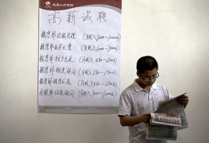 In this photo taken on May 25, 2013, a Chinese man reads the employment newsletters at a job fair held at the China International Exhibition Center in Beijing. While the job market in China is still much better than in many other parts of the world, 2013 is being billed locally as the worst for young graduates. A record number of them _ about 7 million _ are leaving universities and graduate schools to seek their first employment at a time when companies are hiring fewer people. (AP Photo/Andy Wong)